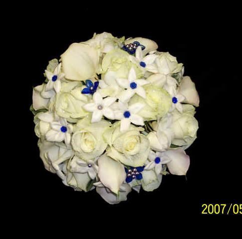 white bouquet featuring roses, stephanotises, mini calla lilies, blue gems