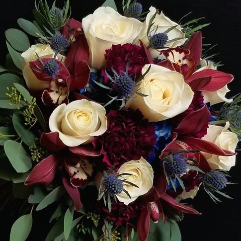 Winter bouquet in burgundy, ivory, blue featuring roses, orchids, carnations, hydrangeas, eryngiums, eucalyptus