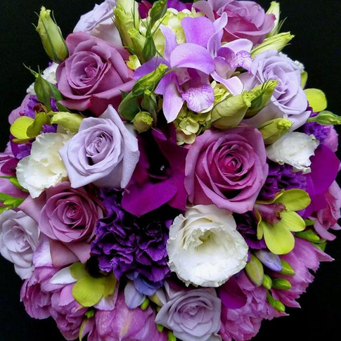 bouquet in shades of purples and touch of white featuring roses, orchids, lisianthus, tulips, freesias, carnations