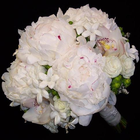 white bouquet featuring peonies, stephanotises, cymbidium orchids, baby roses, green hypericum berries