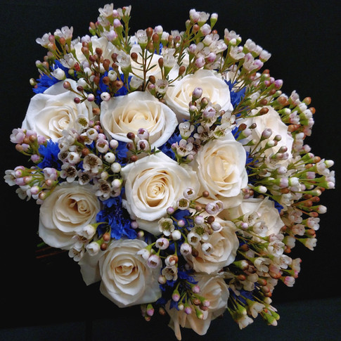 blue and ivory bouquet featuring roses, bachelor buttons, wax flowers