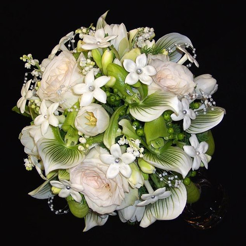 couture bouquet: lilies of the valley, green paphiopedilum orchids, stephanotises, white O'Hara garden roses, cymbidium orchids, tulips, freesias, green hypericum berries, ming fern, pearl loops