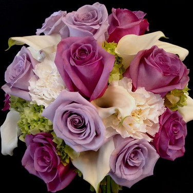 mixed bouquet featuring lavender roses, purple roses, white mini callas, white carnations, green hydrangeas