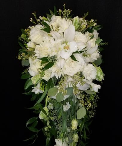 fragrant cascading bouquet featuring tuberoses, roses, orchids, freesias, larkspurs, lisianthus, tulips, lilies, wax flowers, seeded eucalyptus, Italian ruscus