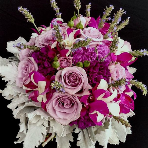 Spring bouquet featuring roses, carnations, orchids, lavenders, dusty milller