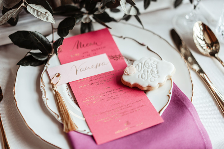 Place card with golden calligraphy and tassel on a hot pink menu with goild foil printing