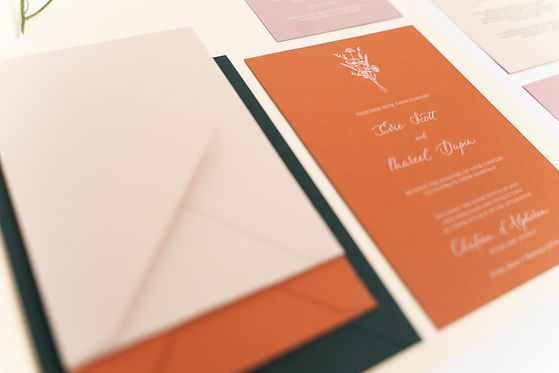 Wedding invitation on rust paper with white ink calligraphy and wildflowers illustrations, part of a semi custom collection