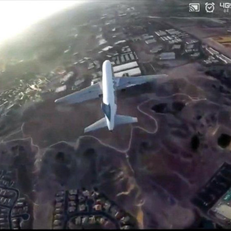 Drone flies above a commercial jet
