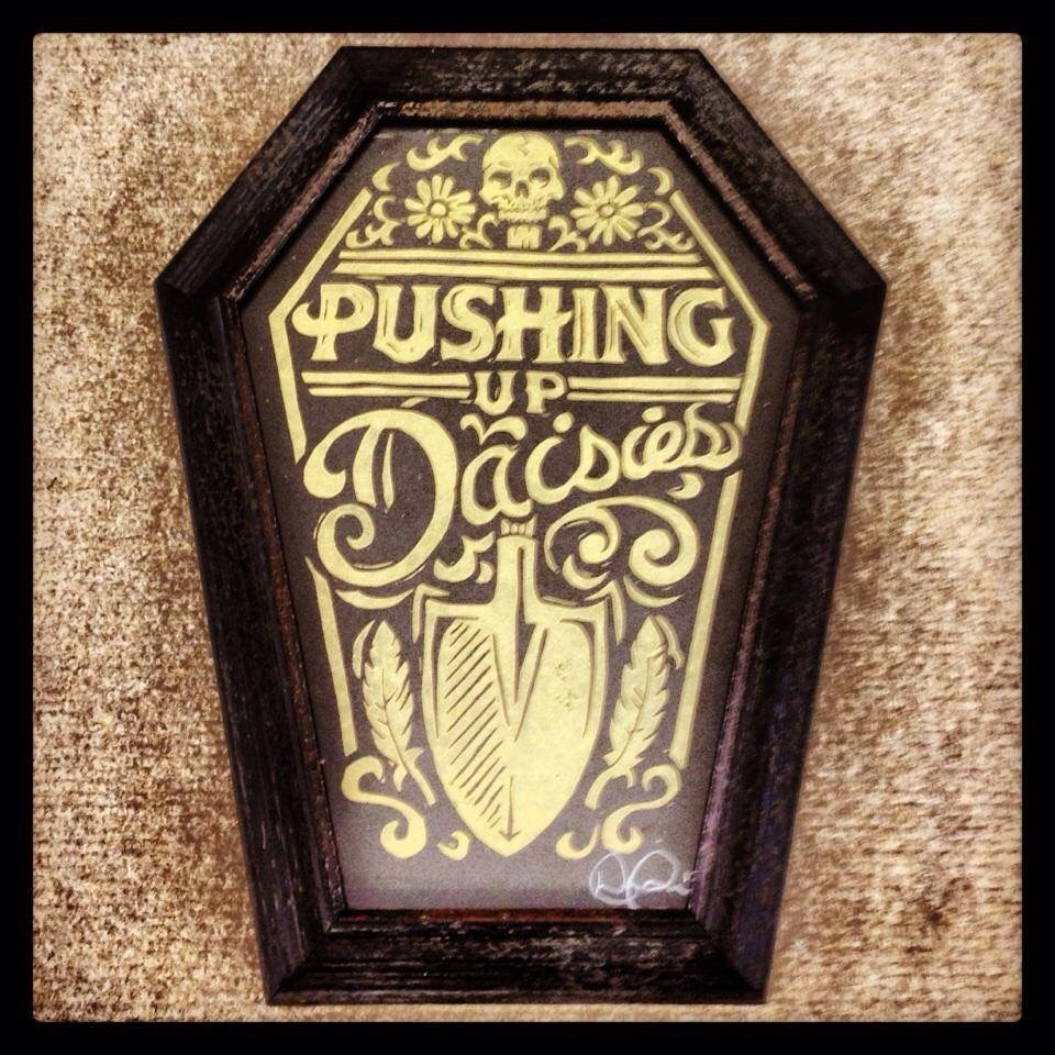 Coffin shaped frame around a strawcastle original block print pushing up daisies