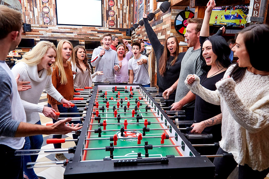 A group shot of people playing eight person foosball. Some people are showing excitement while others show disappointment for losing