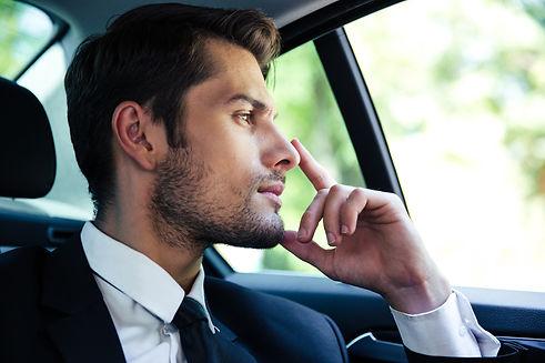 Thoughtful businessman riding in car.jpg