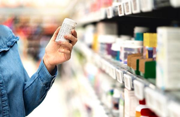 Customer in pharmacy holding medicine bo