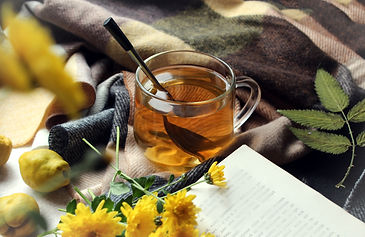 A Cup of tea with a book and yellow flowers.