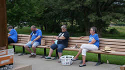 Picnic guests social distance while listening