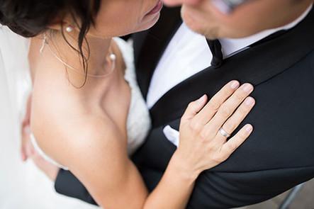 Detail Eheringe Braut kuschelt an Bräutigam