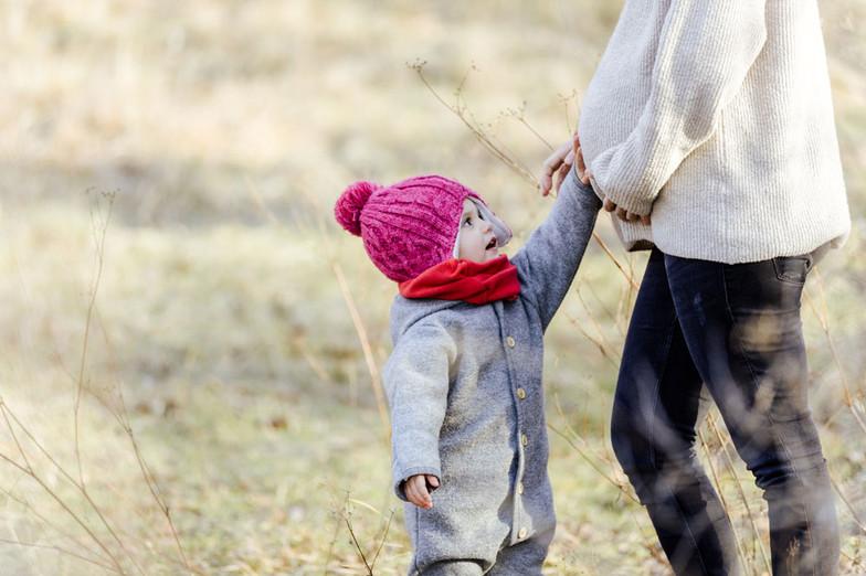 Schwangerschaft Babybauch werdende Mama mit Kind im Winter