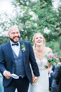 Braut und Bräutigam beim Auszug mit Seifenblasen