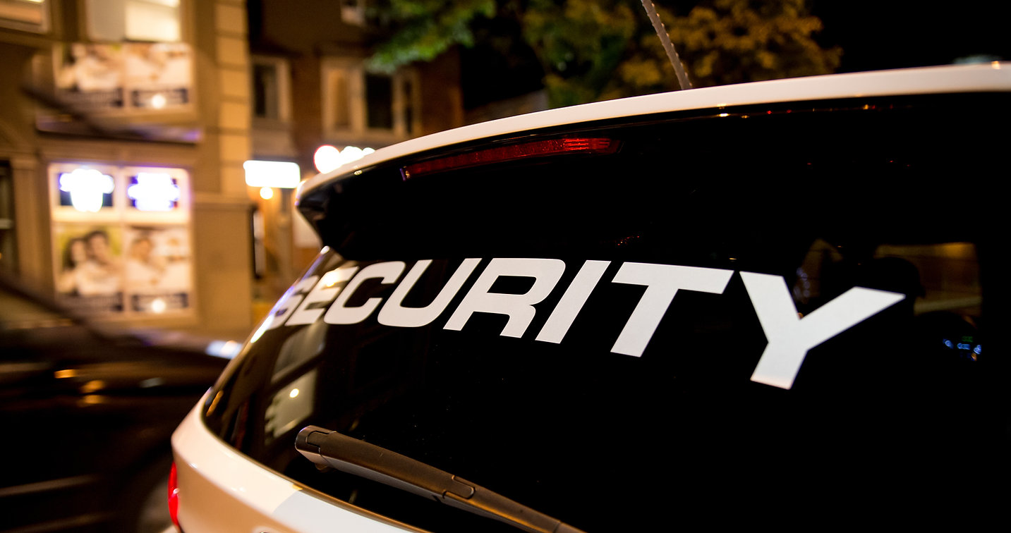 Security Guard Group vehicle patrolling city at nigh