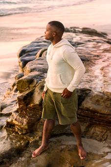 Julian standing on sea rocks.
