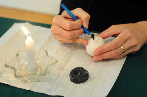 Using the kistka, the melted wax is applied onto areas of the white egg