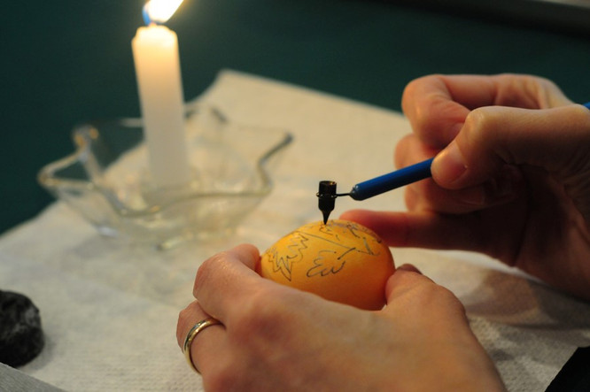 Melted wax is now applied to areas of the yellow-colored shell that are to be yellow