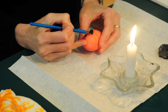 Melted wax is now applied to areas of the orange-colored shell that are to be red