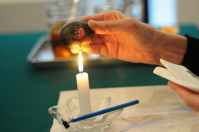 Melting the beeswax by holding the egg close to the candle flame, wax melts and colors reappear and a pysanka is born