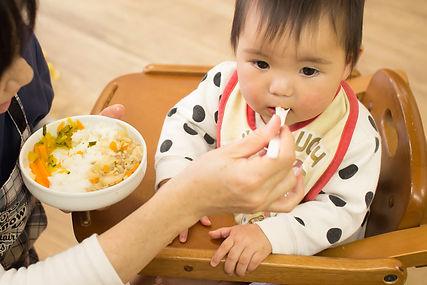 保育士が給食の時幼児に離乳食を食べさせる