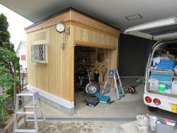 木のガレージにシャッターと窓を設置します。