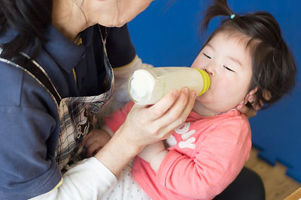 保育士が園児にミルクを飲ませる