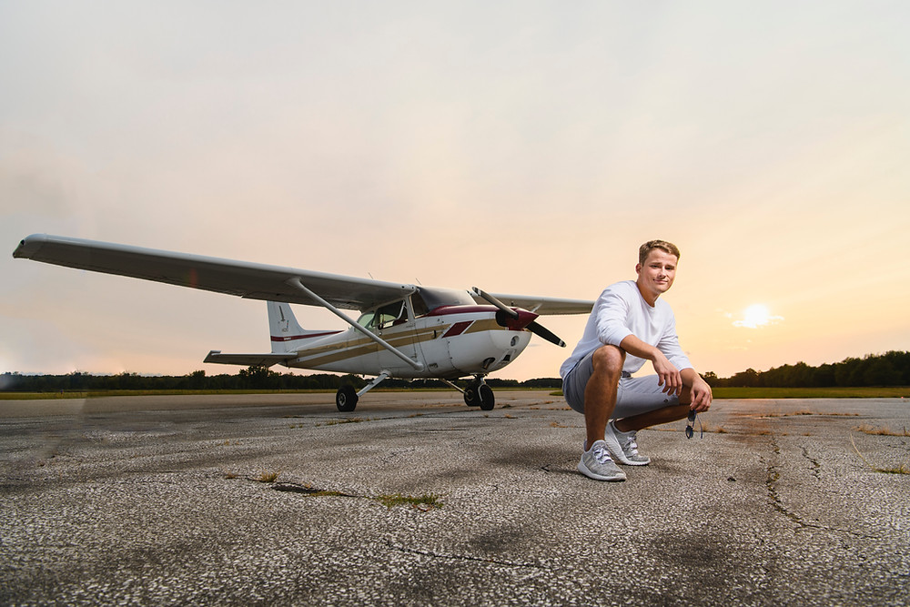 Senior Portrait Picture of guy posing in front of airplane.