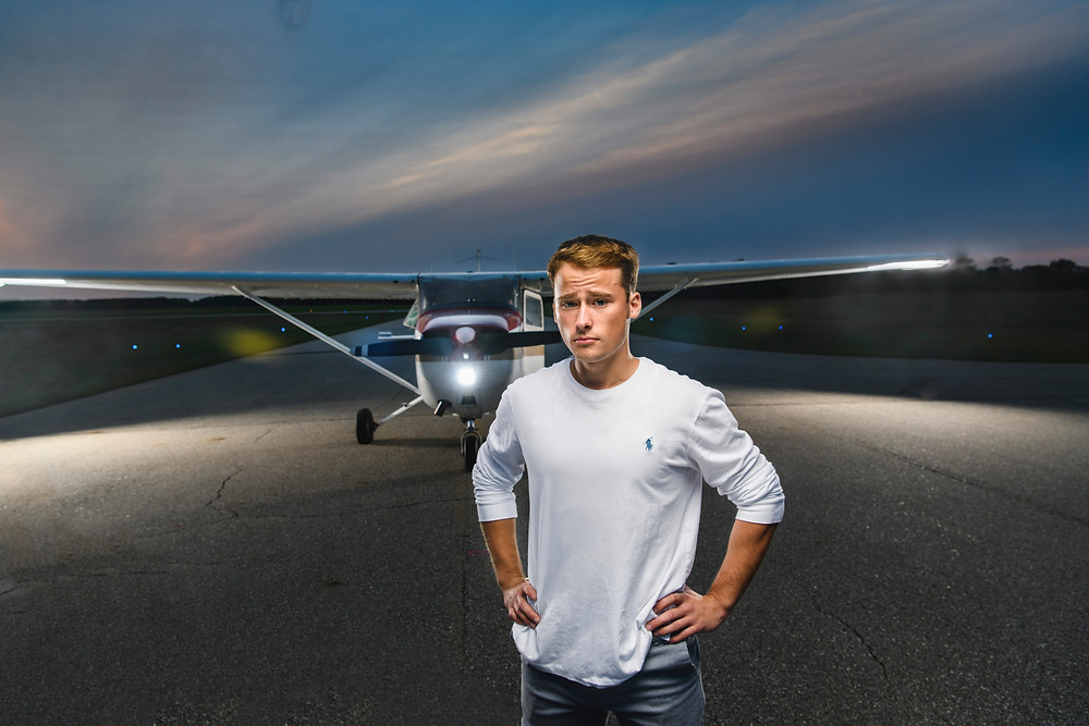 Senior guy posing with airplane in portrait by Charis Seed Photography