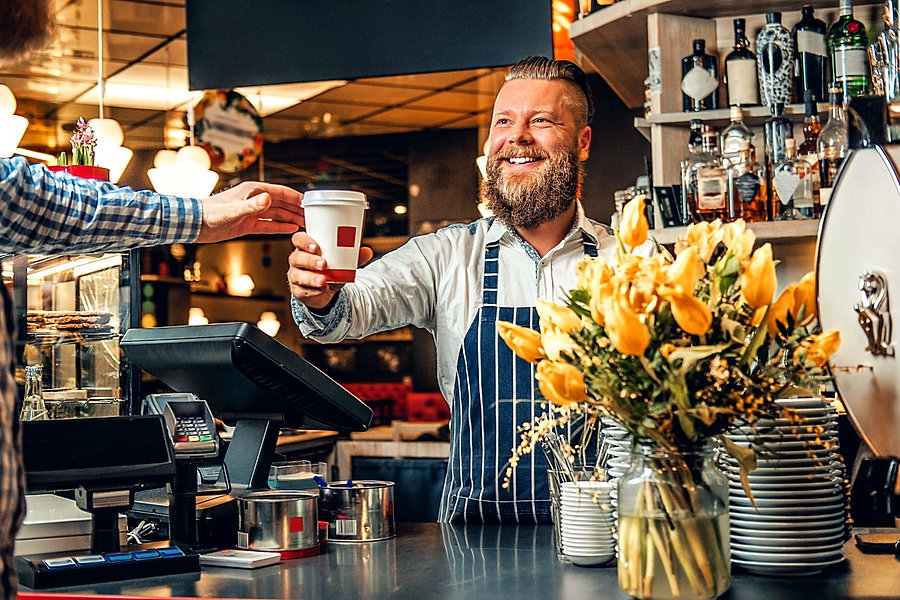 Positive bearded barista male selling coffee to a consumer in a coffee shop._edited.jpg