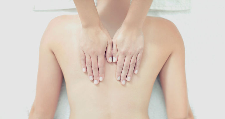 Hands treating a back