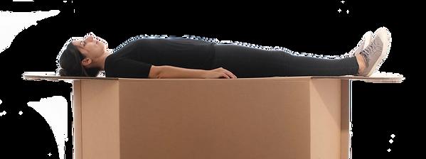 Paciente reclinado sobre cama de cartón recibiendo asistencia médica.