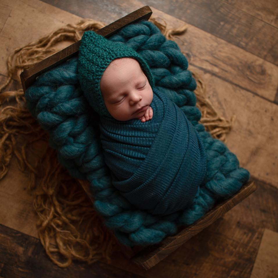 newborn boy in bed