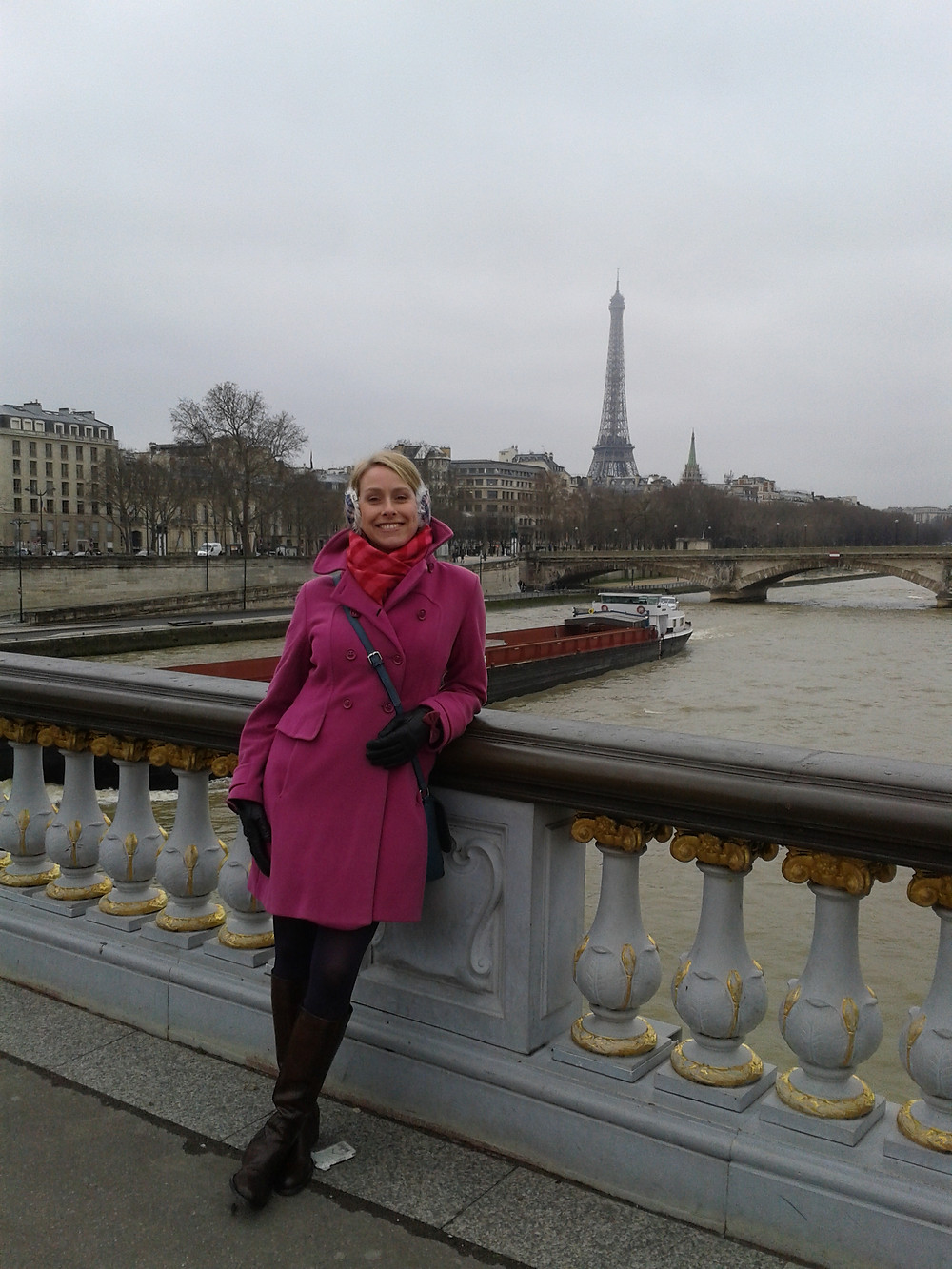 Shelley Kelly on a bridge in Paris in a pink coat ending at mid thigh