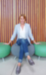 Shelley Kelly  in jeans and blazer sitting on stools personal stylist