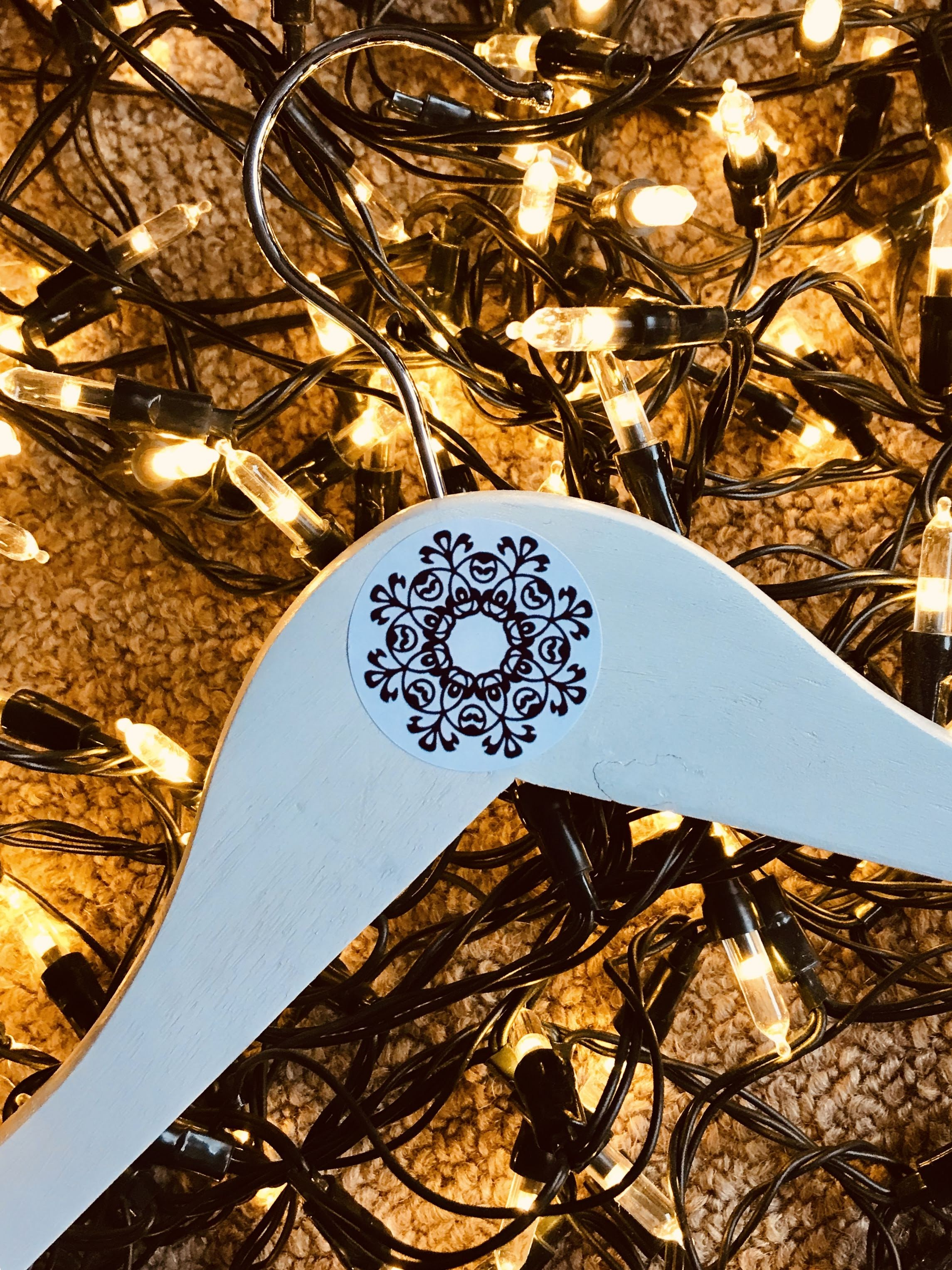 White wooden coathanger with Shelluey Kelly Style sticker against fairy lights