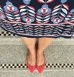 Shelley Kelly. Red shoes on a patterned staircase. Patterned dress