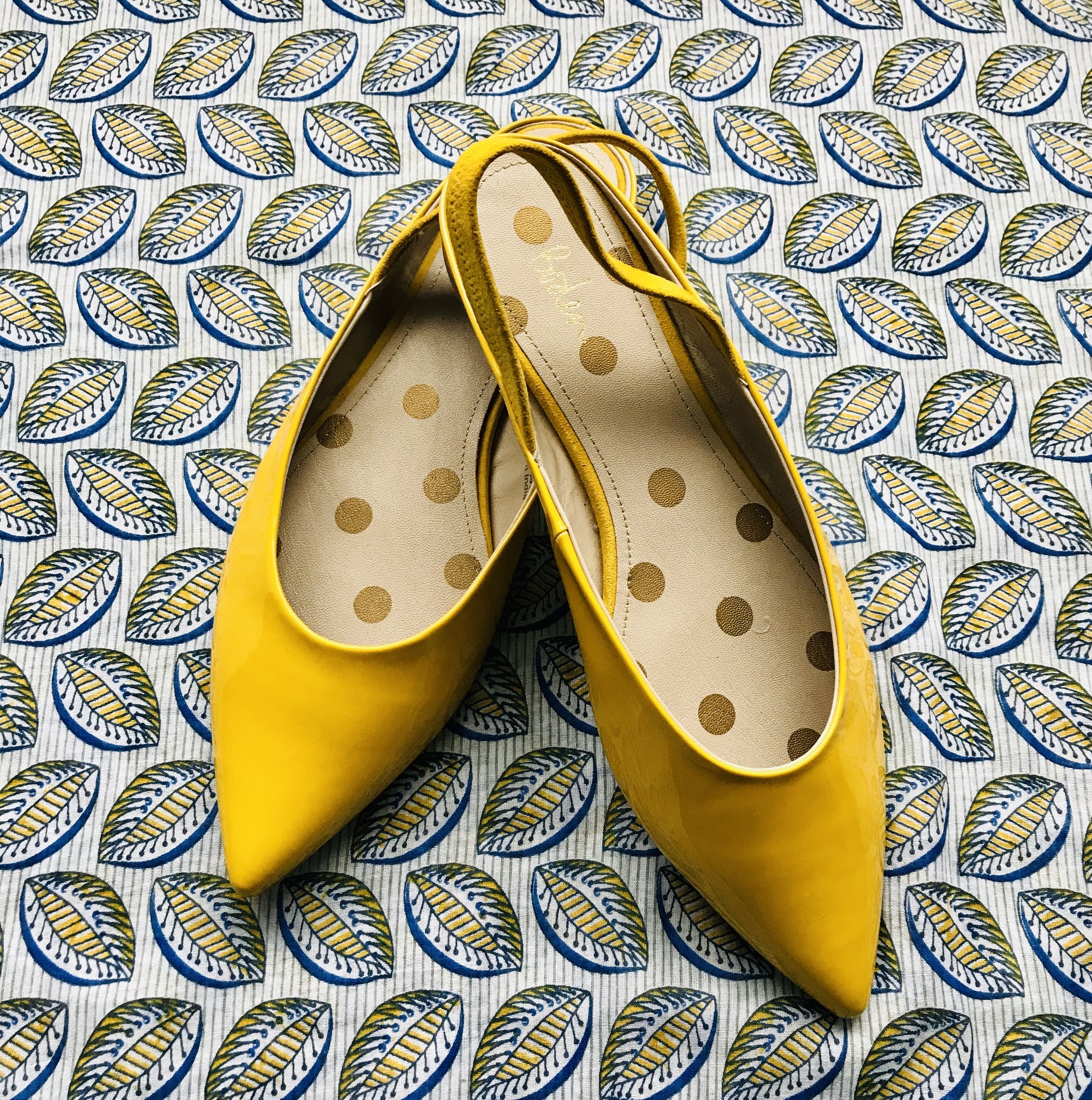Yellow patent sling back flat shoes from Boden on a yellow and blue patterened scarf