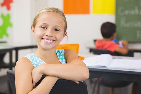 portrait-cute-little-girl-sitting-desk.j