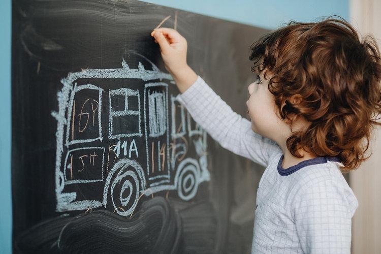 curly-little-boy-draws-chalk-board-his-r