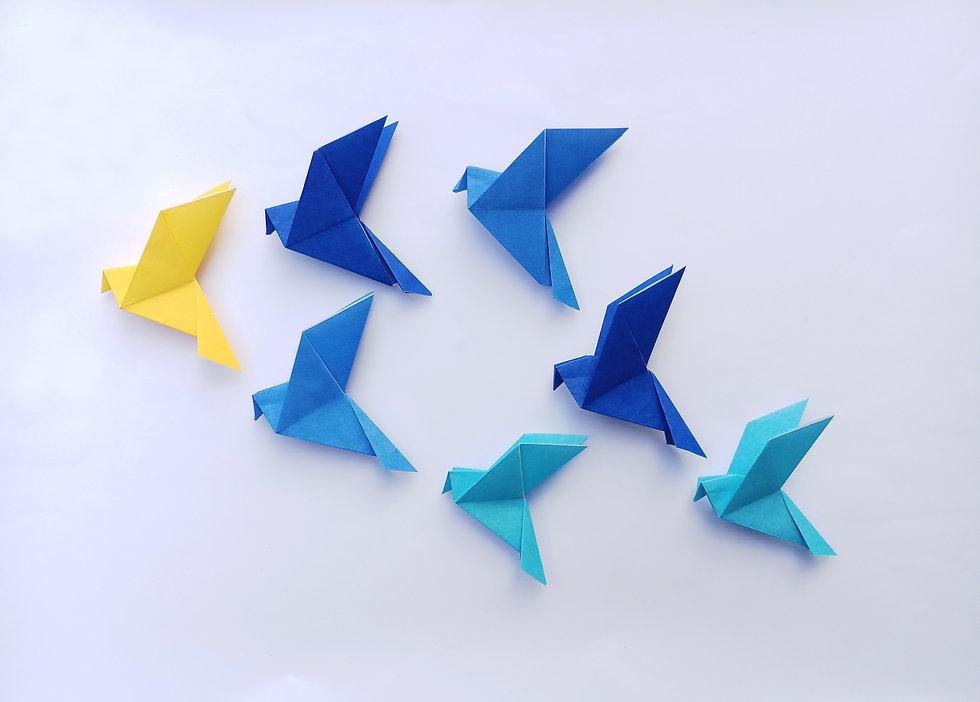 Seven blue origami  birds are flying lea