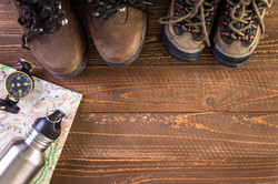 Hiking shoes with topo map and compass on a wood background