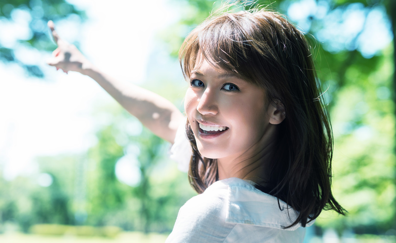 Asian girl pointing finger outwards