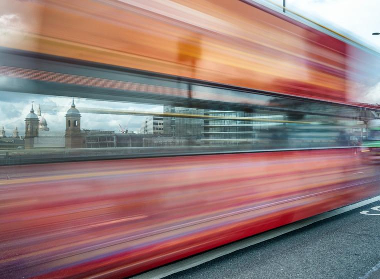 Red Bus trail along a city bridge