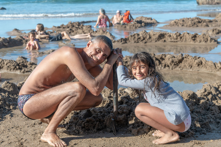 Father and daughter building a pool in Hot Water Beach, New Zealand