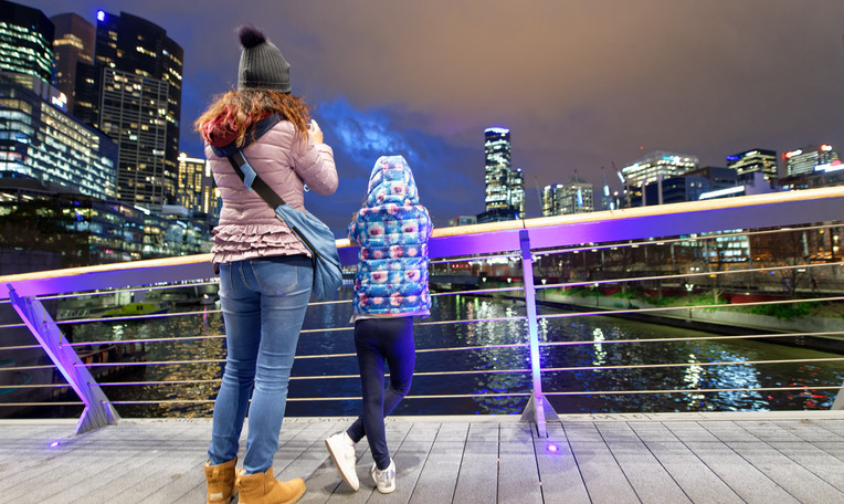 Mother and daughter looking at Melbourne skyline at night, Australia