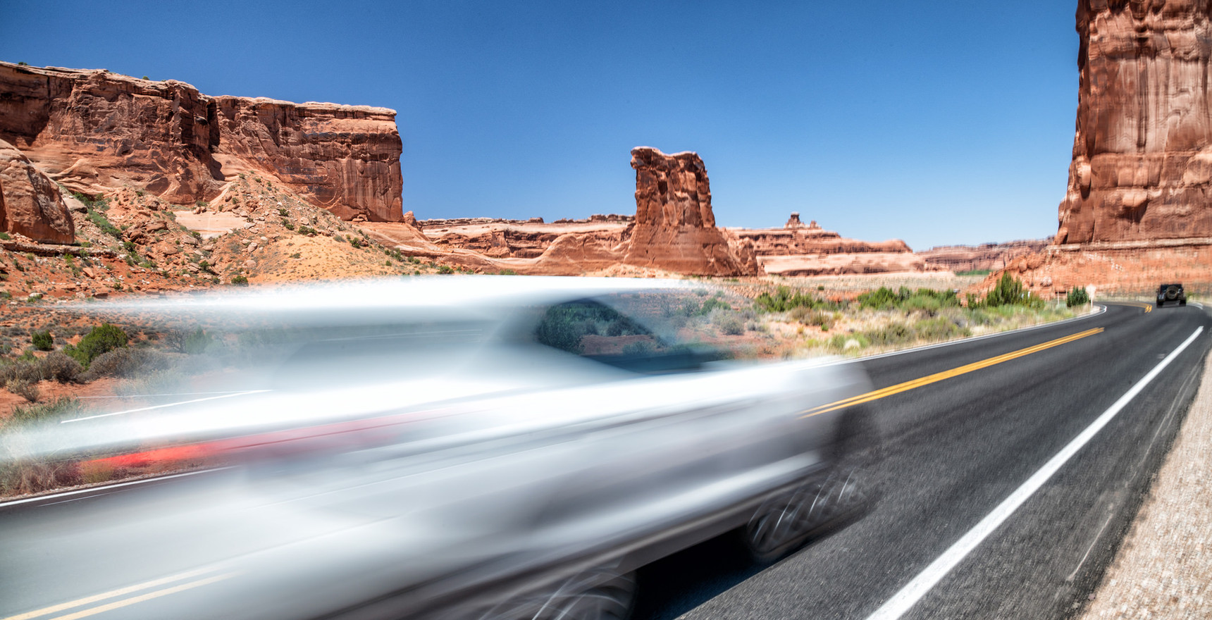 White car speeding up in a National Park, USA